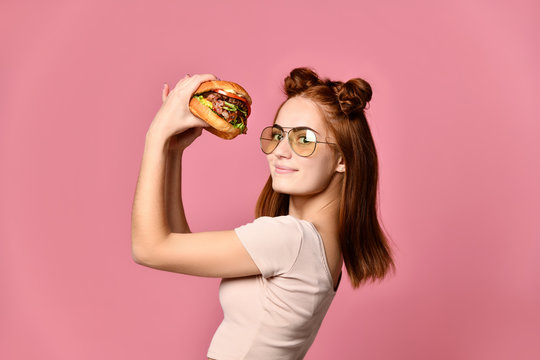 Woman eat burger sandwich with hungry mouth on pink background.