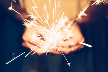 Close up hand woman holding sparklers in night party and christmas celebration.