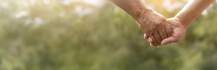 Fototapeta Senior couple holding hands together over green nature background. obraz