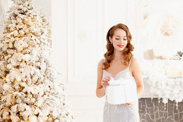 Dream Christmas present concept. Beautiful young woman in silver dress gift against background of New Year tree and fireplace, white color