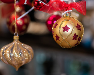 Two hanging Christmas ornaments in gold and silver with red stars and ribbon