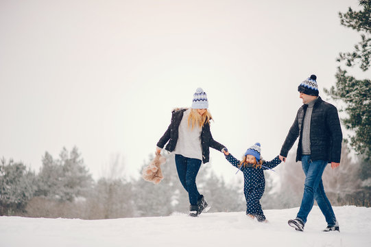 Family have fun in a winter park. Stylish mother in a blue jacket. Little girl in a winter clothes. Father with cute daughter