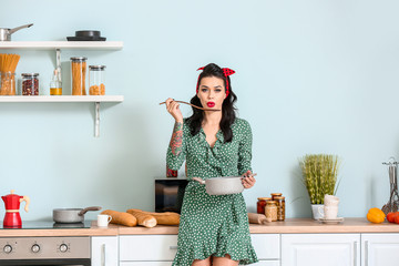 Portrait of beautiful pin-up woman cooking in kitchen