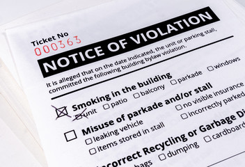 Notice of violation ticket for building bylaws. Close up. No smoking in the building has a check mark. Strata or rental property management tool to warn about smoking, parking and recycling.