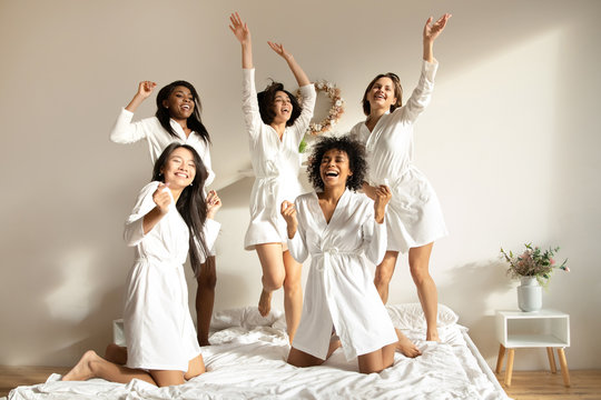 Excited multiracial girls friends having fun dancing on bed