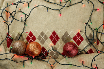 Frame from a New Year's garland and balls on a knitted sweater. Christmas background