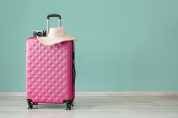Suitcase, photo camera and hat near color wall. Travel concept