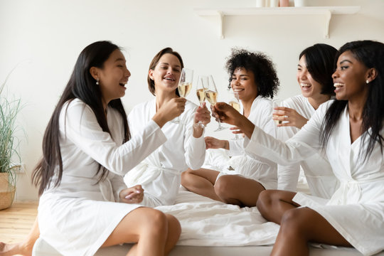 Excited diverse girls friends wear robes celebrating clinking champagne glasses