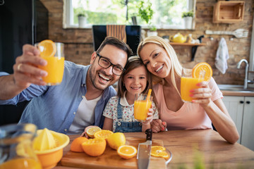 Cheerful young family drinking orange juice