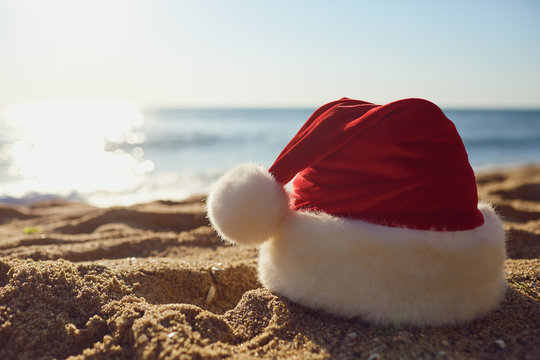 Santa Claus hat on the beach by the sea.
