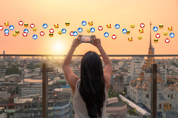 Woman taking a photo with a phone during the sunset. Emojis in the air for social media sharing