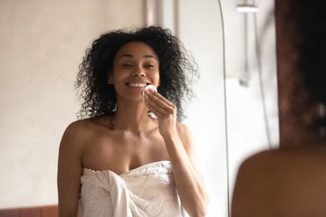 Smiling african American woman do facial treatment in bathroom