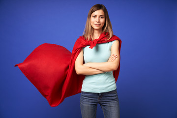 Woman in red superhero cloak standing on empty blue background