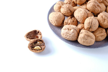 Walnuts in a bamboo bowl on a white board.
