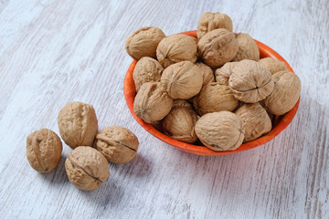 Walnuts in a bamboo bowl on a white wooden board.