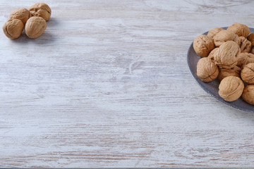 Ceramic plate with nuts on white wood.