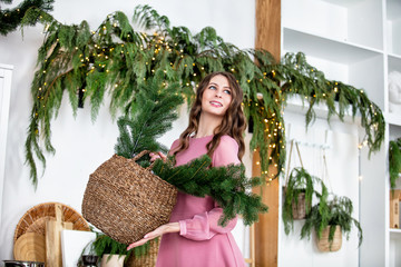 Beautiful happy young adult brunette girl in dress portrait in room with fir branches in basket