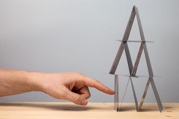 Hand breaks the house of cards