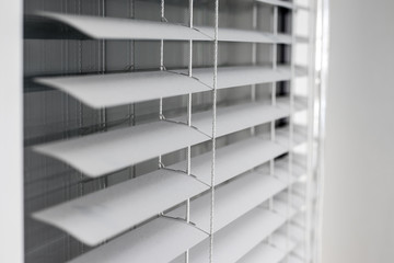 white window blinds with reflections on the glass