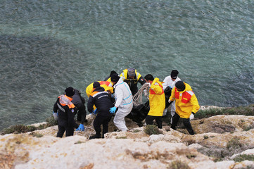 Rescue workers bring bodies to shore after a migrant boat capsized off the Italian coast, on the island of Lampedusa