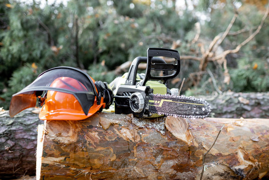 Electric chainsaw and protective hardhat on the wooden log in the forest, Concept of a professional logging with chainsaw
