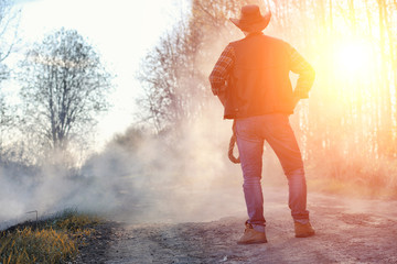 A man is wearing a cowboy hat and a loso in the field. American farmer in a field wearing a jeans hat and with a lasso in the smoke of a fire. A man walks through a burning field