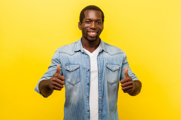 Thumbs up, excellent job! Portrait of enthusiastic handsome man in denim casual shirt with rolled up sleeves smiling and showing like gesture at camera. studio shot isolated on yellow background