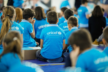 Children wearing Unicef shirts take part at an event. Unicef logo.