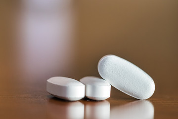 Close -up of three pills with oval shape on a table, selective focus