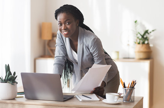 Afro Businesswoman Working With Documentation And Laptop In Modern Office