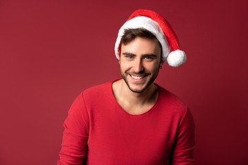 Young handsome caucasian guy in red sweater and Santa hats stands on red background in studio and...