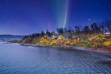 norwegian house on a small island Oslo archipelago with Aurora in the sky