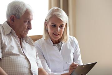 Pleasant middle aged female doctor explaining medicine prescription to patient.