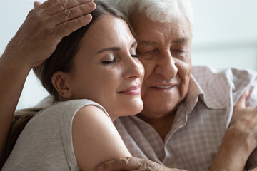 Older hoary man hugging loving grown up daughter at home.