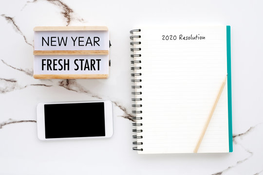 20120 resolution on blank notebook paper, smart phone with blank screen on white marble background, 2020 new year mock up, template, flat lay