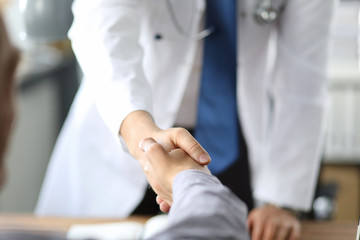 Closeup image of healthcare professional or doctor or dentist shaking hands with patient.