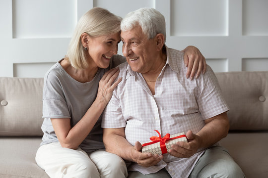 Happy older 70s man feeling thankful to wife for present.