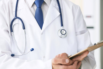 Close-up of clipboard with blank paper in medical doctor hand. Male doctor listens to the patient holding a clipboard with documents for hospitalization.