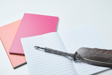 colored notebooks, open scratch pad and writing pen.