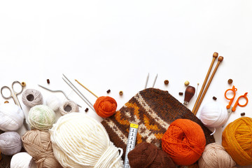 Top view on knitting accessories: balls of wool yarn, knitting needles, hooks, scissors, pins and hand knitted hat on a white background. Copy space, flat lay, mock up