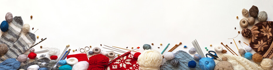 Top view of knitting accessories, balls of wool yarn and handmade knitted warm hats, scarves and mittens. Needlework concept, long banner, white background, flat lay, copy space, mock up