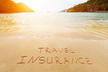 Travel insurance and cover of accidental risk concept. Handwriting drawing on sand. Scenic view on beautiful summer tropical beach of harbor.