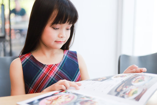 Asian little girl reading book smile and happy face