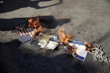 Representations of a U.S. and Israeli flag and a picture of U.S. President Donald Trump are set on fire during a protest near the U.S. Embassy in Awkar