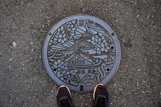 OSAKA, JAPAN -NOVEMBER 05, 2019: manhole cover in Osaka, Japan. Osaka castle embossed on a manhole cover as a symbol of city . Drain cap japanese style on walkway in Osaka, Japan