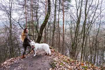 Young woman hiking in a forest with white swiss shepherd