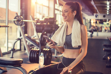 Beautiful fitness woman with smart phone and towel relaxing after sports training at gym