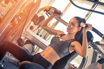 Beautiful fitness girl working out on exercise machine at gym