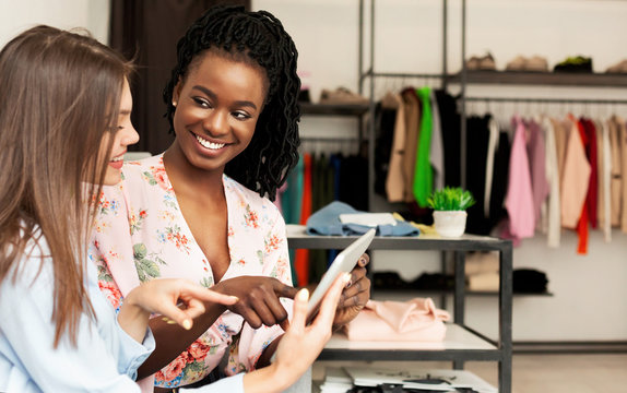 Shopping Assistant Using Tablet Helping Client Buy Clothes In Store