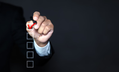 Checklist concept, Businessman checking mark on the check boxes with marker red